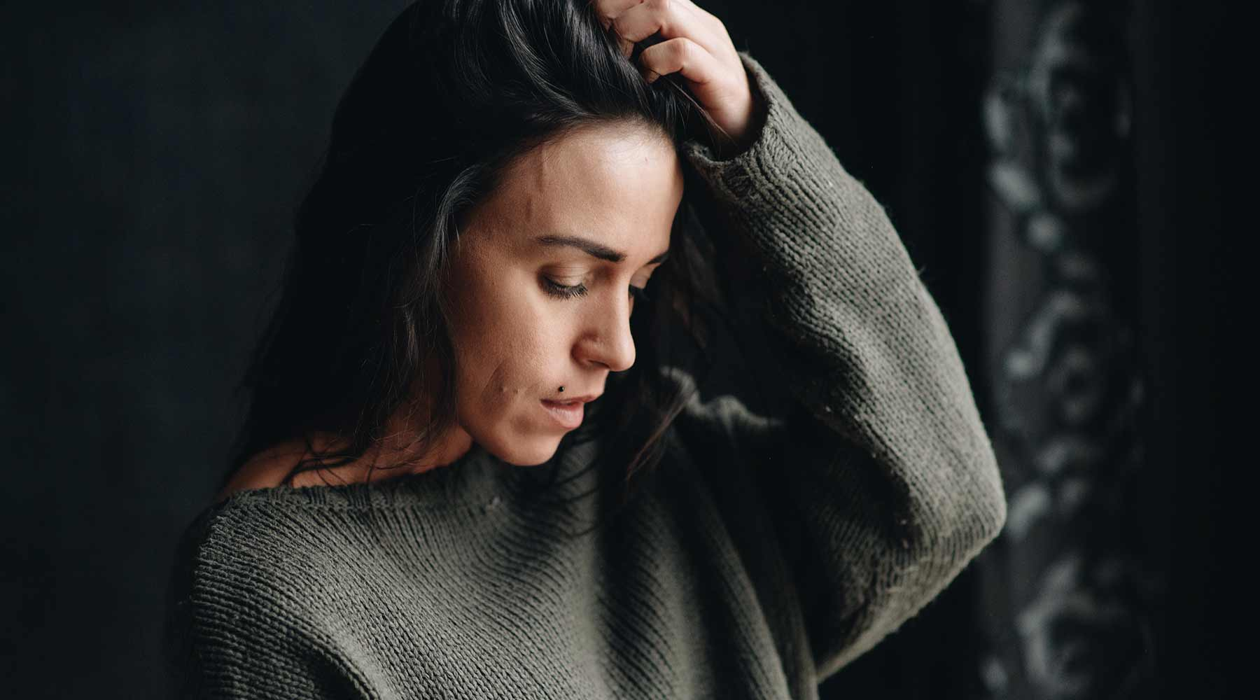 Woman in moss green sweater running hand through long dark hair, showing signs of worry, tiredness, anxiety.