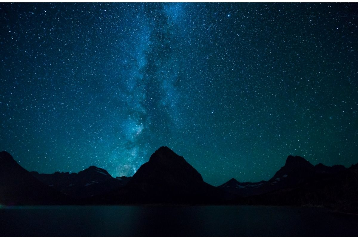 Mountain peaks and a bright starry night sky in Glacier National Park, one of many International Dark Sky parks