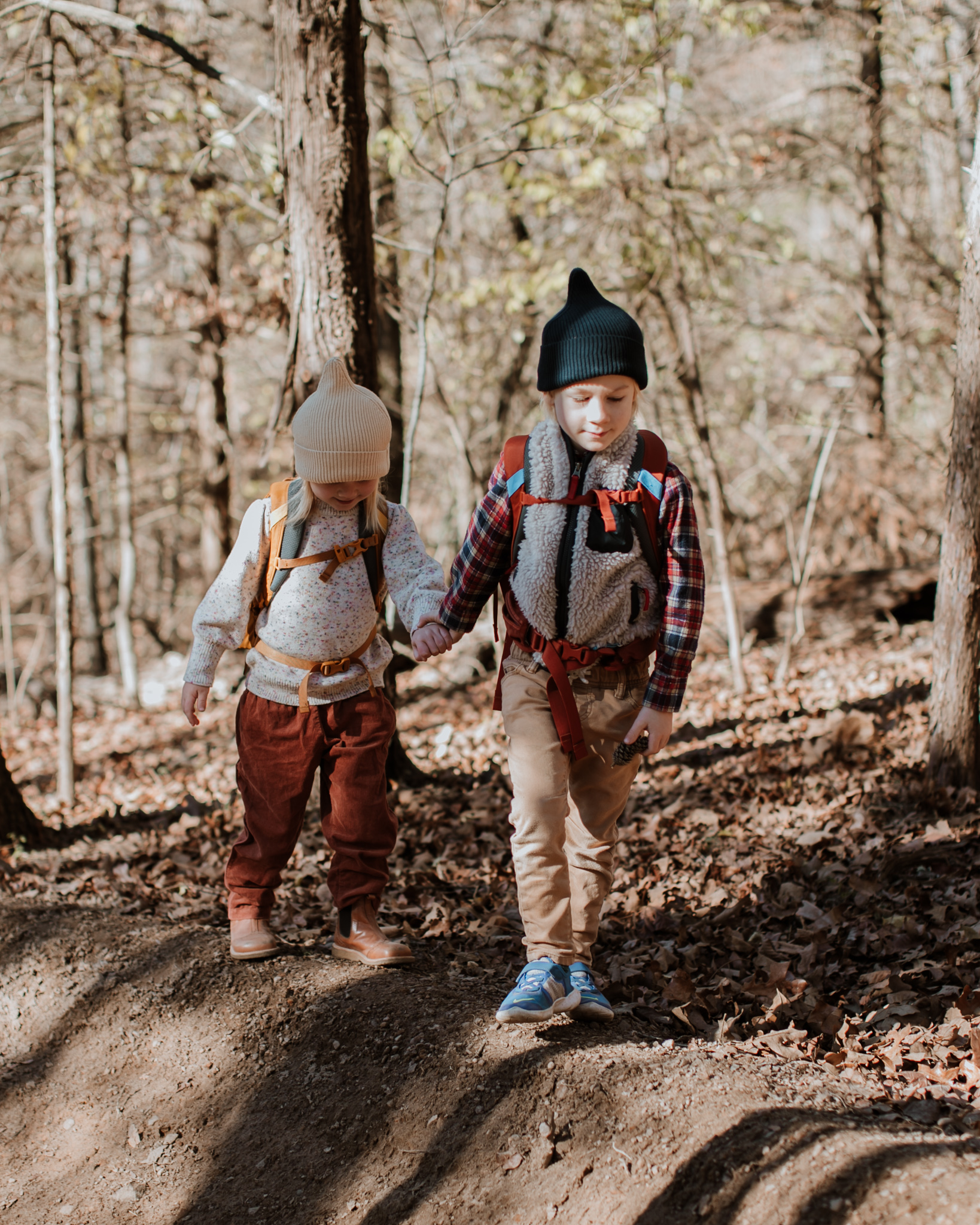 Two children hiking in a bare winter forest.