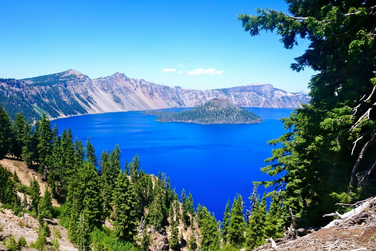 Deep blue Crater Lake and several trees surrounding its perimeter