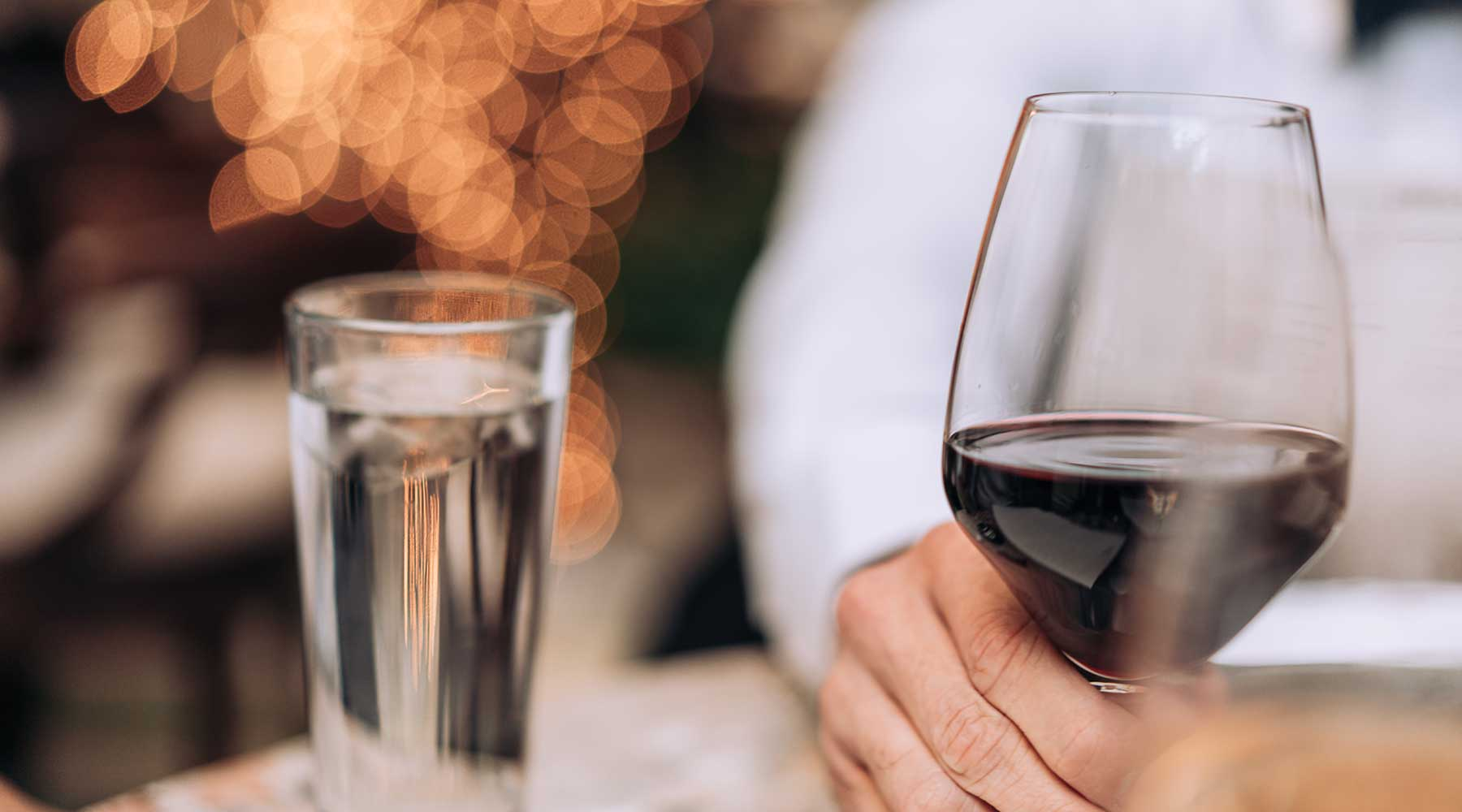 Man at restaurant, drinking a glass of red wine. Glass of water next to wine..
