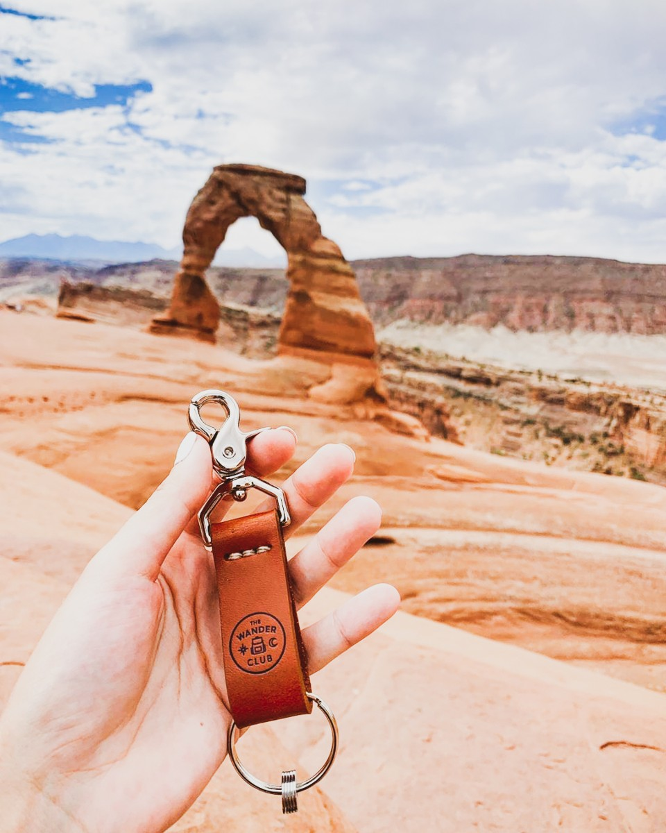 A hand holding a keychain and tokens from The Wander Club in front of Delicate Arch in Arches National Park