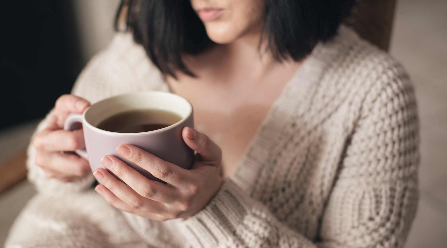 Woman in beige cable knit deep v neck sweater holding a cup of tea.