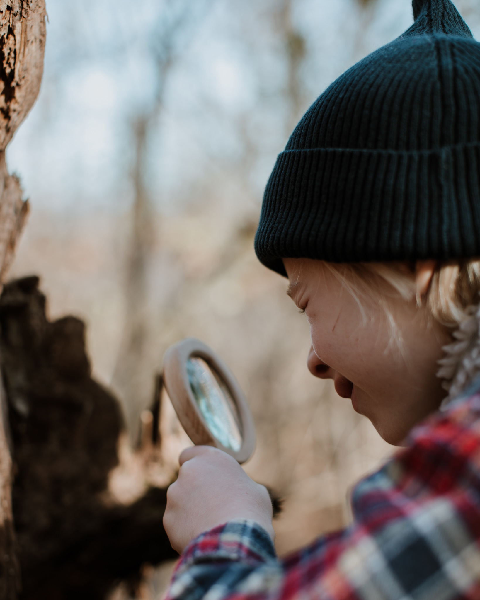 A child looking through a wooden magnifying glass.