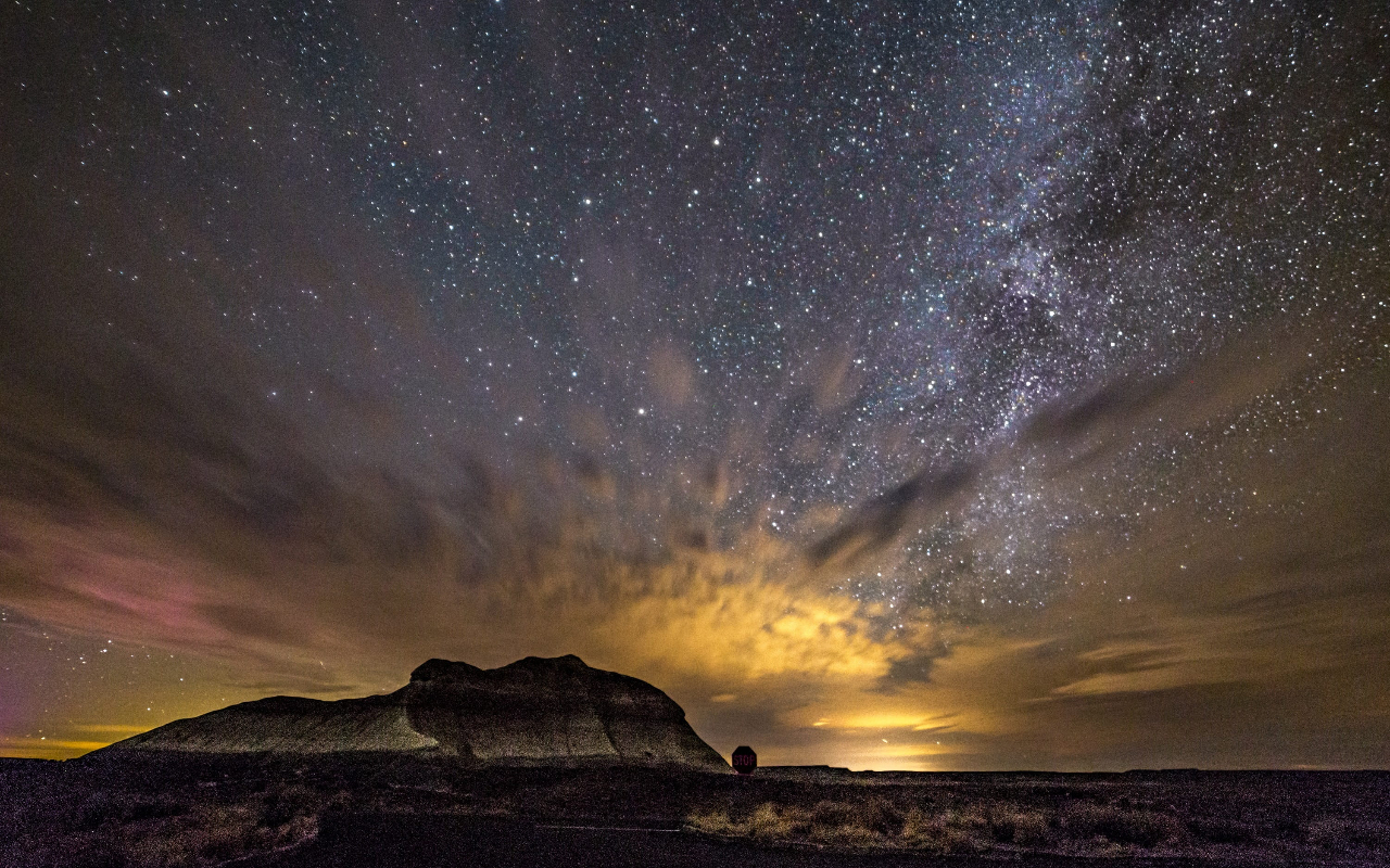 A large rock formation in the starry night sky in Petrified Forest National Park, one of several spectacular International Dark Sky Parks