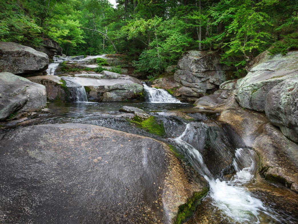 Rippling through a 24-acre preserve managed by the Mahoosuc Land Trust, Step Falls slides right into a swimming hole surrounded by granite slabs.