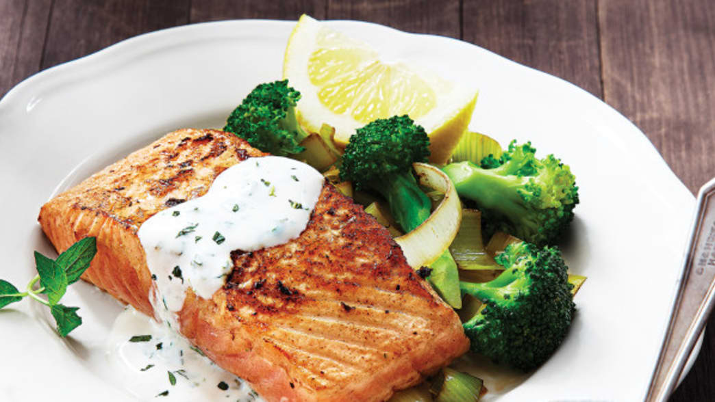 Image by Clean Eating Magazine - Alaskan Salmon plated with vegetables and a sauce on top