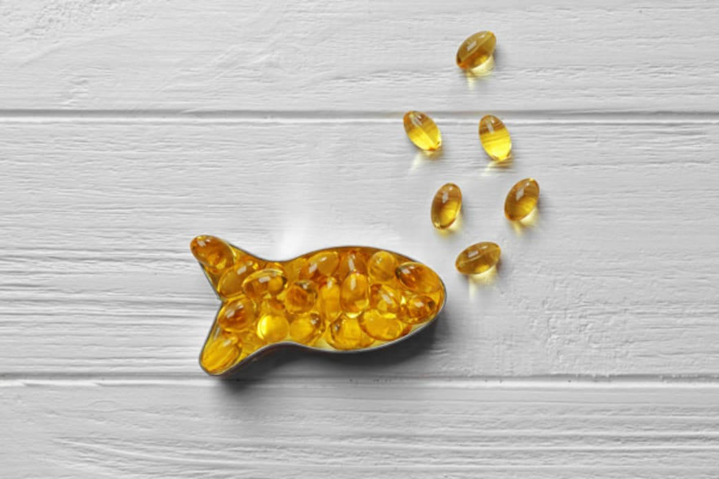 .Better Nutrition - Fish shape container with fish oil supplements in it.