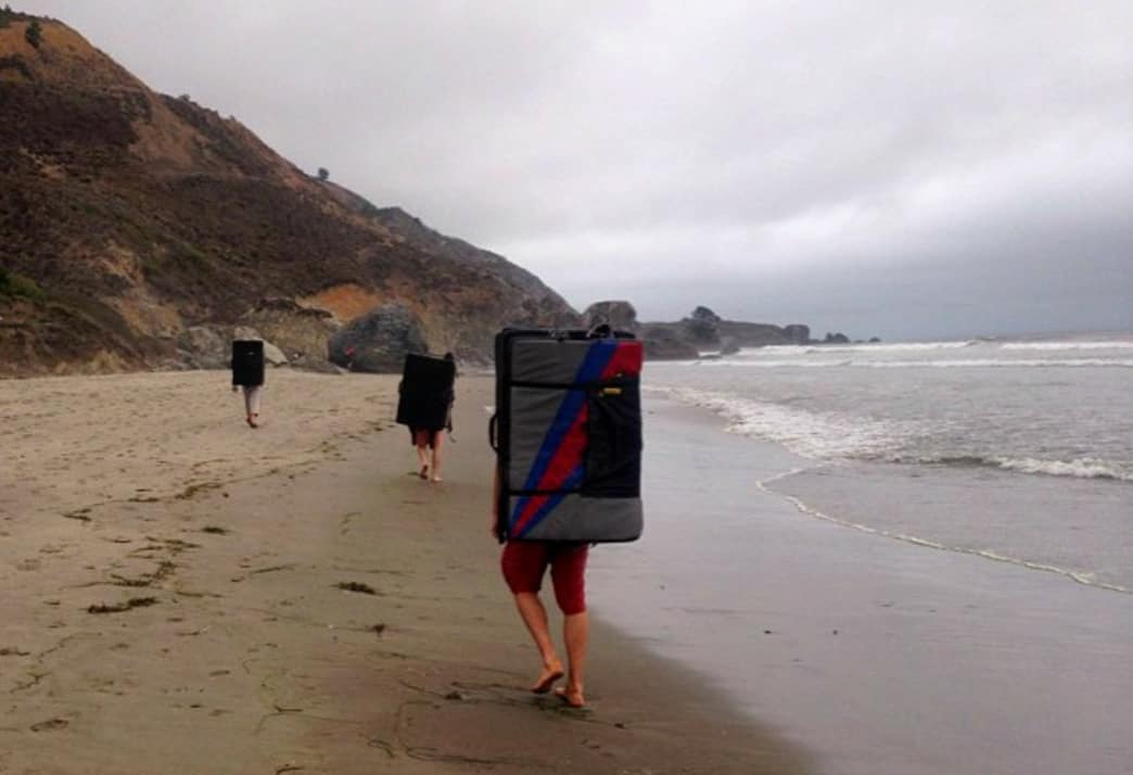 Three climbers head out to the boulders at Stinson Beach