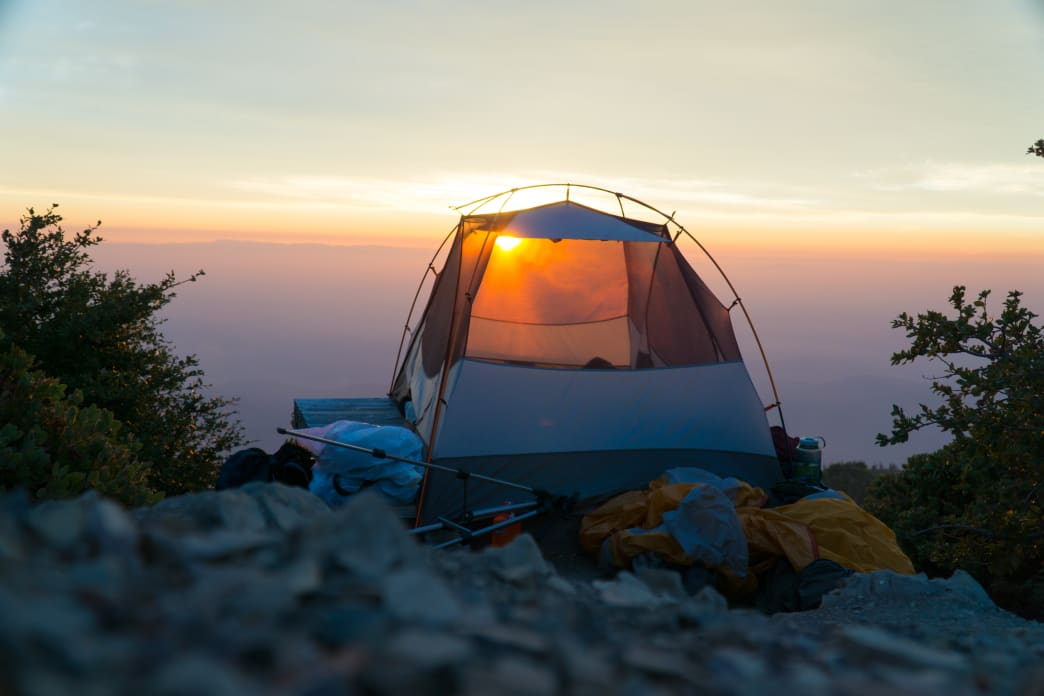 Tent on cliff edge at sunrise