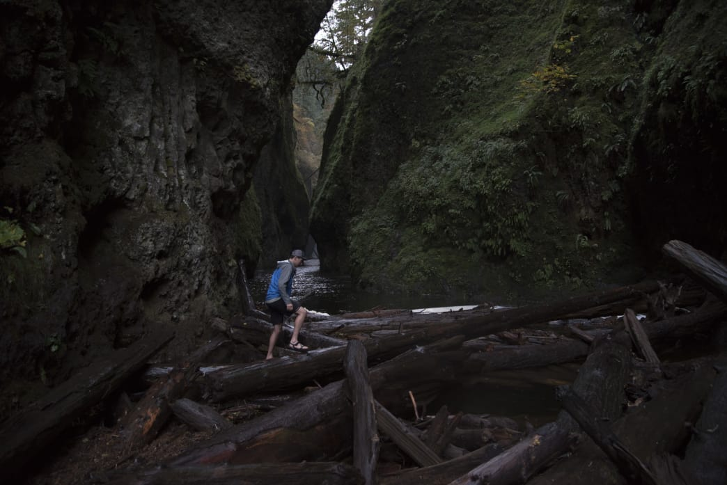 Hiking over a slippery logjam in Oneonta Gorge.