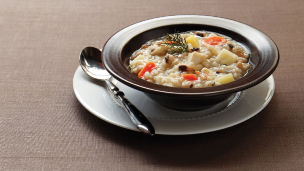 .Bowl of slow cooker chicken barley stew - Clean Eating Magazine