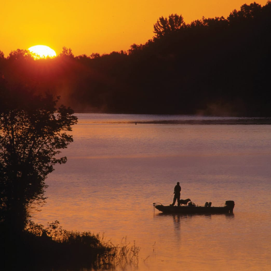 Man with dog on boat fishing TN River at sunrise