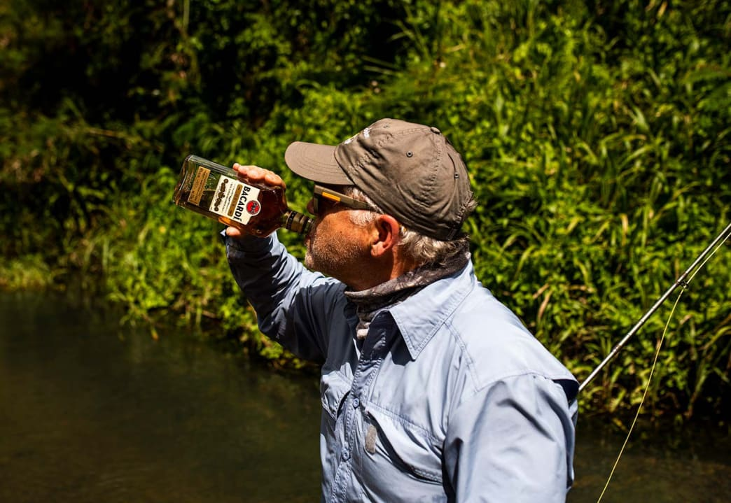 The author sips some celebratory rum after landing his first mountain mullet.
