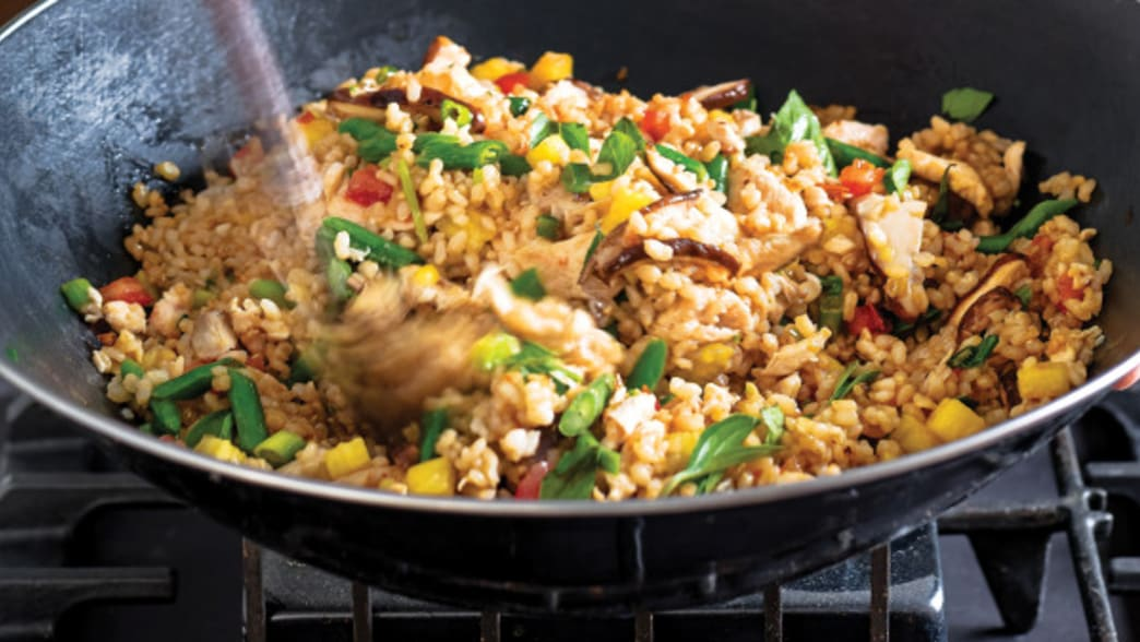 Wok with Chicken Fried Rice with Pineapple being stirred - Clean Eating Magazine