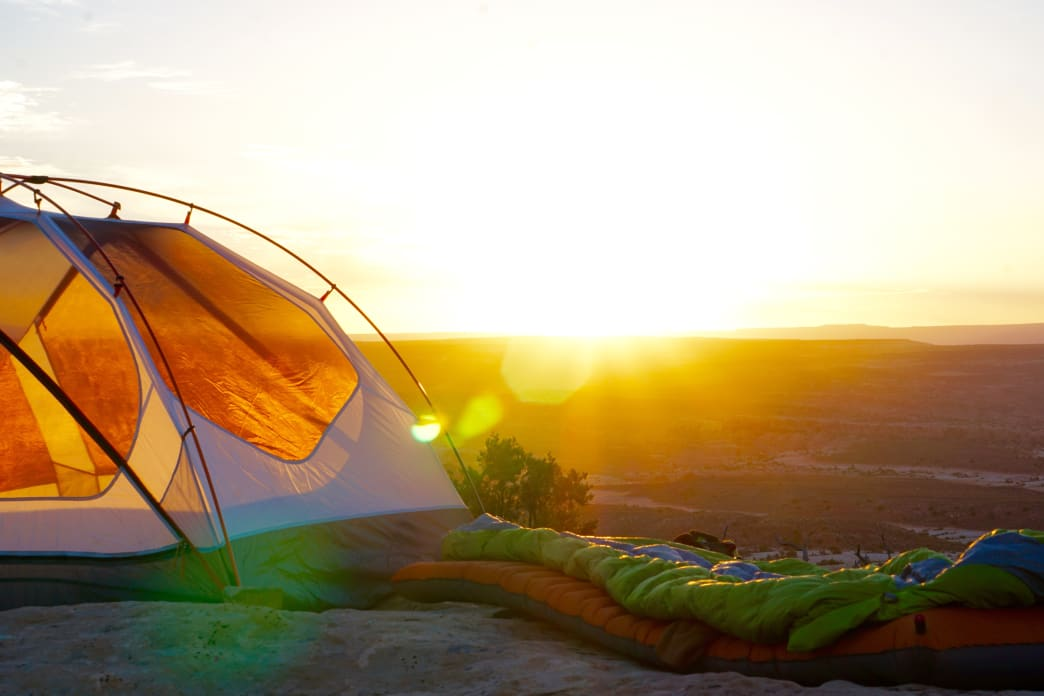 Backpacker enjoying the sunset outside of their tent after a long day's hike
