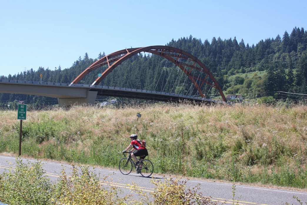 Cycling is a popular pastime on Sauvie Island. The Sauvie Island Bridge (behind the cyclist) was completed in 2008 and is the only way to get on or off the island.