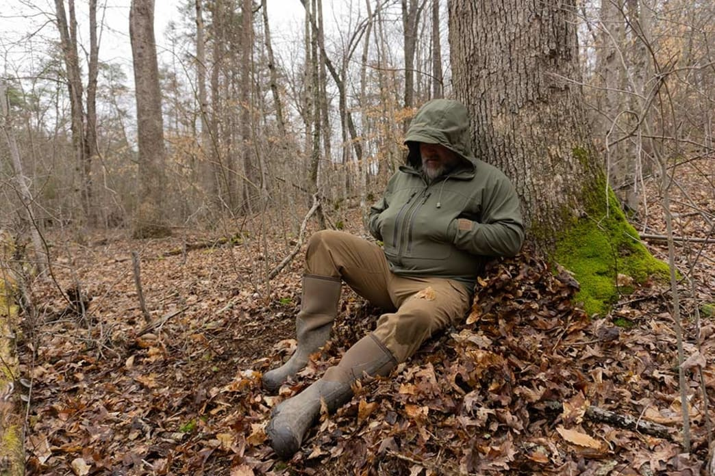 hunter sitting on a pile of leaves