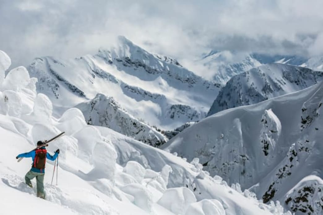 Bootpacking Skier with skis over shoulder looks at canadian snowy vista