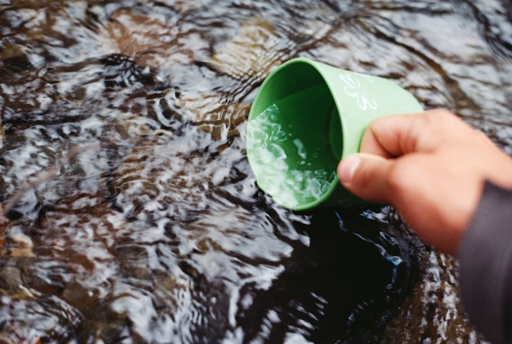 Hand holding a green mug in a stream