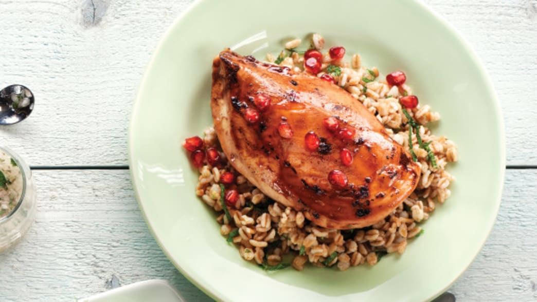 Plated Lime pomegranate chicken breasts with herbed farro - Clean Eating Magazine