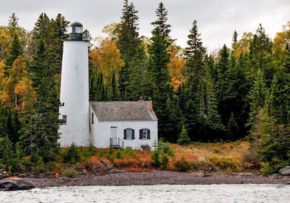A white lighthouse and turning fall foliage in Michigan's Isle Royale National Park, included on a list of fun facts about national parks